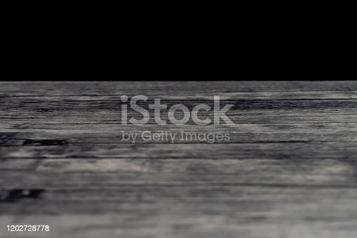 1151171813 istock photo Wooden table top with defocus black wall background 1202728778