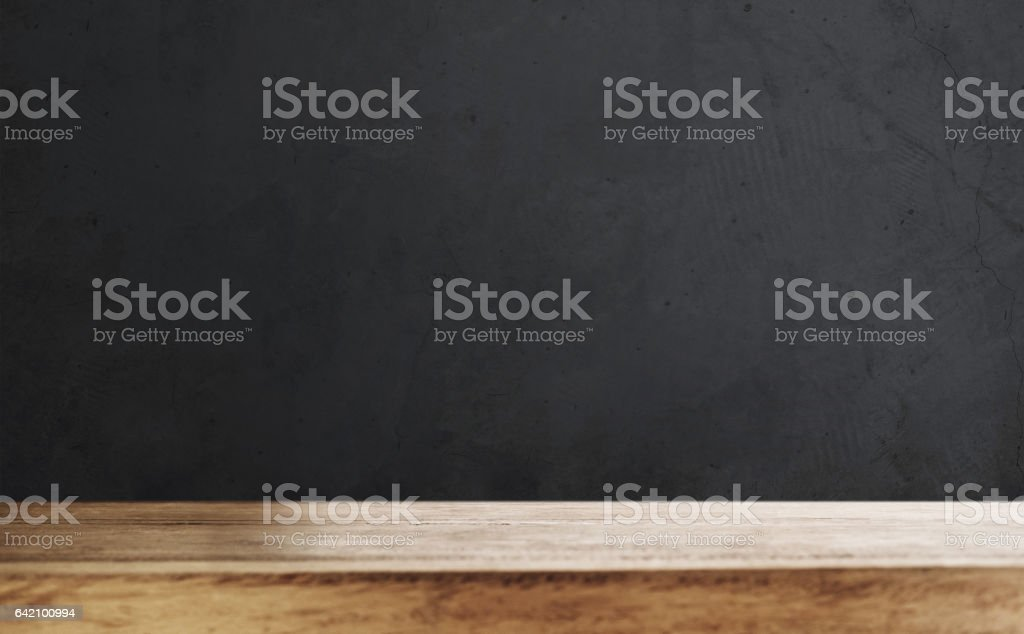 Wooden table top with defocus black wall background stock photo