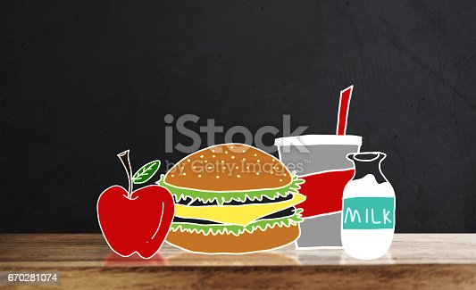 1077234988istockphoto Wooden table top with drawing breakfast, Hamburger, apple, juice and milk, on black wall backgrounds 670281074