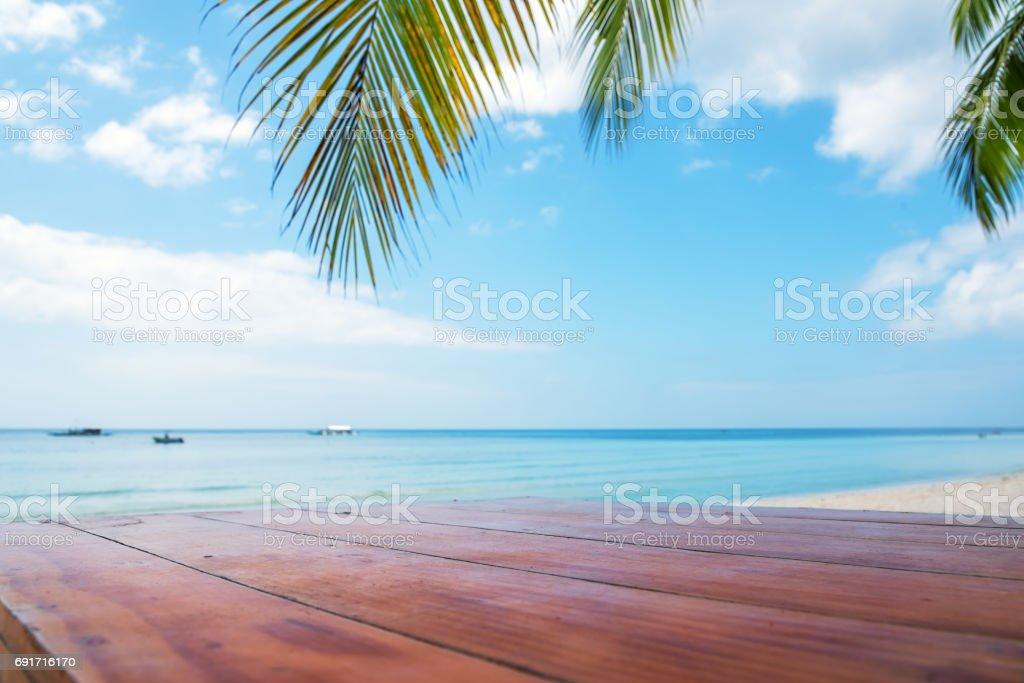 Mesa de madeira sob a palmeira de praia tropical - foto de acervo