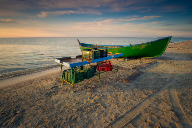 Wooden table used by the fishermen to sort the fish before selling it when they arrive from fishing with crates on and under the table and a wooden boat on the Black Sea Coast in Romania at Corbu, Constanta County stock photo