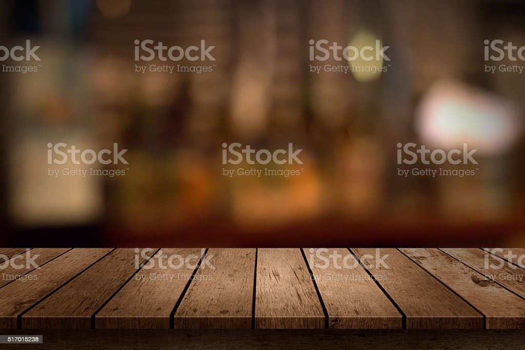 wooden table with a view of blurred beverages bar backdrop royalty-free stock photo