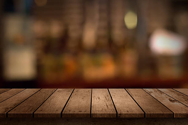 wooden table with a view of blurred beverages bar backdrop stock photo