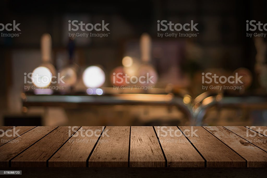 wooden table with a view of blurred beverages bar backdrop stok fotoğrafı