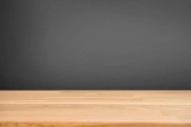 Holztisch mit unscharfen schwarze dunkle Wand Hintergrund. – Foto