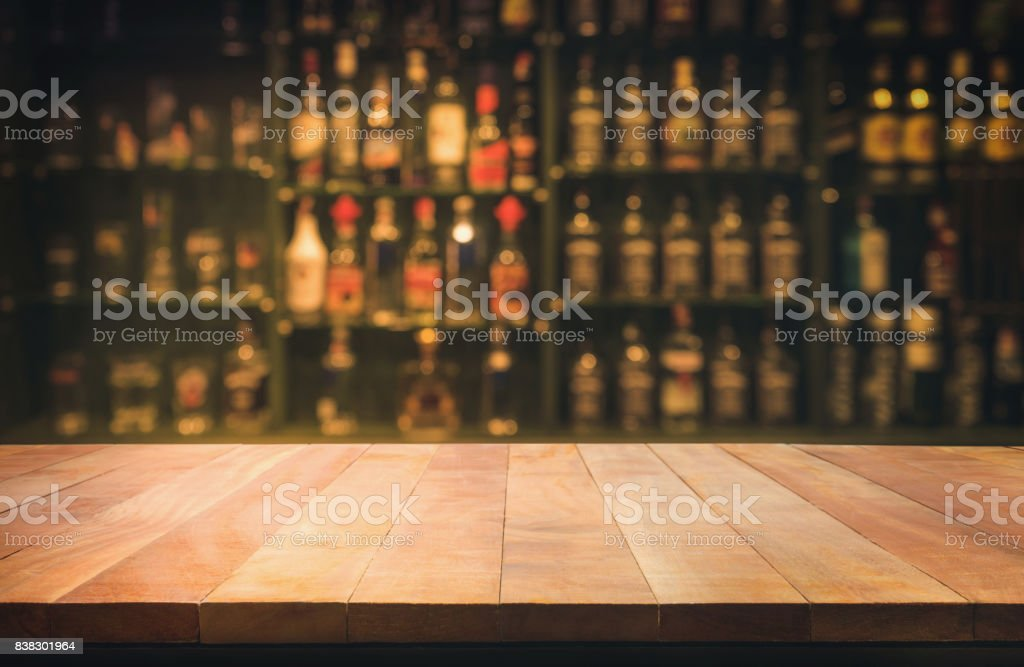 wooden table with blurred counter bar and bottles Background stock photo