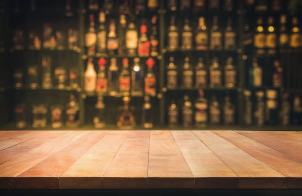 wooden table with blurred counter bar and bottles background - beer alcohol stock pictures, royalty-free photos & images