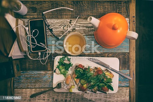 istock Wooden table with cell phone, cup of tea, bright orange teapot, glasses and dietary vegetable salad, top view, vintage 1183825862