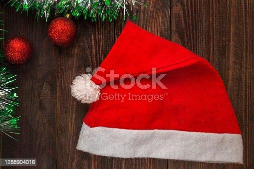 wooden table with Christmas balls, garland and santa hat. Flatlay