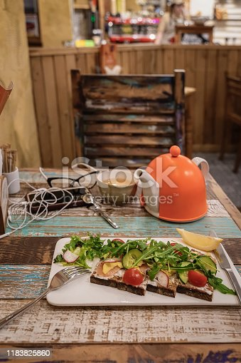 istock Wooden table with dietary vegetable salad, cell phone, cup of tea, bright orange teapot, glasses in cafe 1183825860