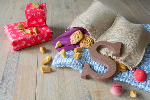 houten tafel met nederlandse sinterklaas snacks in jute zak, met gebreide servet, taai taai, geschenken - cadeau sinterklaas stockfoto's en -beelden