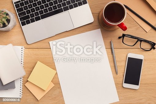 Male workplace with empty sheet of paper for advertisement, smartphone with blank screen, laptop, coffee cup and glasses. Wooden background, top view, mockup, copy space.