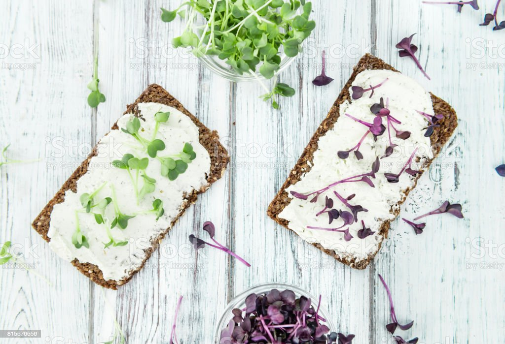 Wooden table with healthy food (slice of bread, cream cheese and fresh cutted cress) stock photo