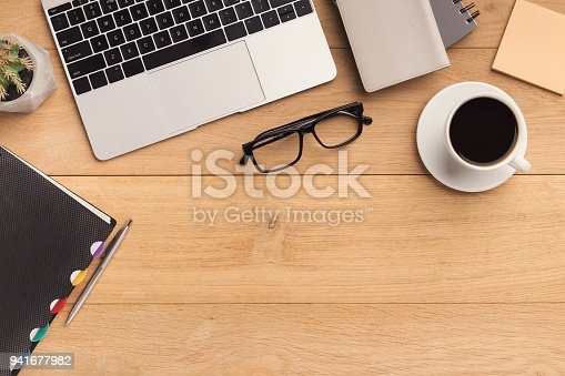 istock Wooden table with laptop top view, copy space 941677982