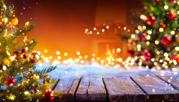 Wooden Table With Snow And Defocused Christmas Tree - Abstract Background stock photo