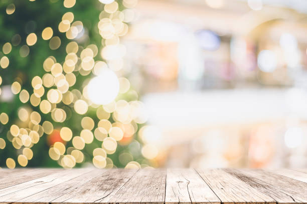 Wooden table with space with Christmas tree and blurred light bokeh for mock up or montage your product advertisement. stock photo