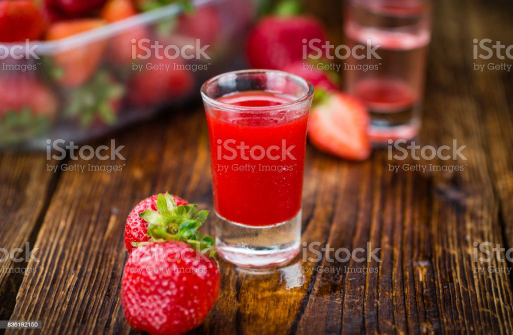 Wooden table with Strawberry liqueur, selective focus stock photo