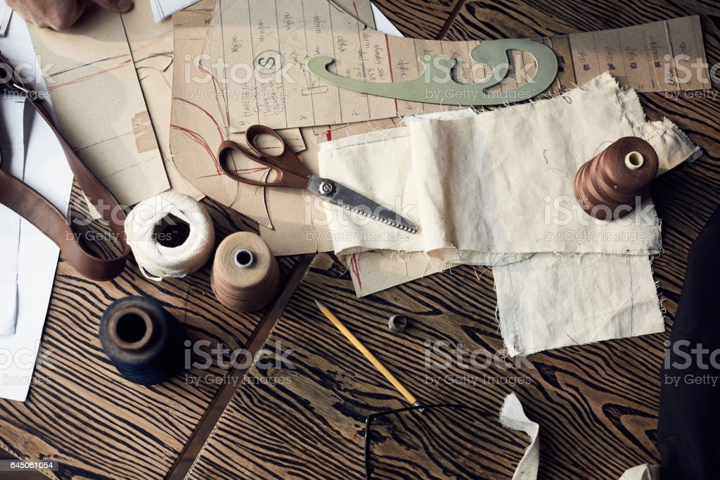 Wooden table with treads, scissors and other tailoring equipment stock photo