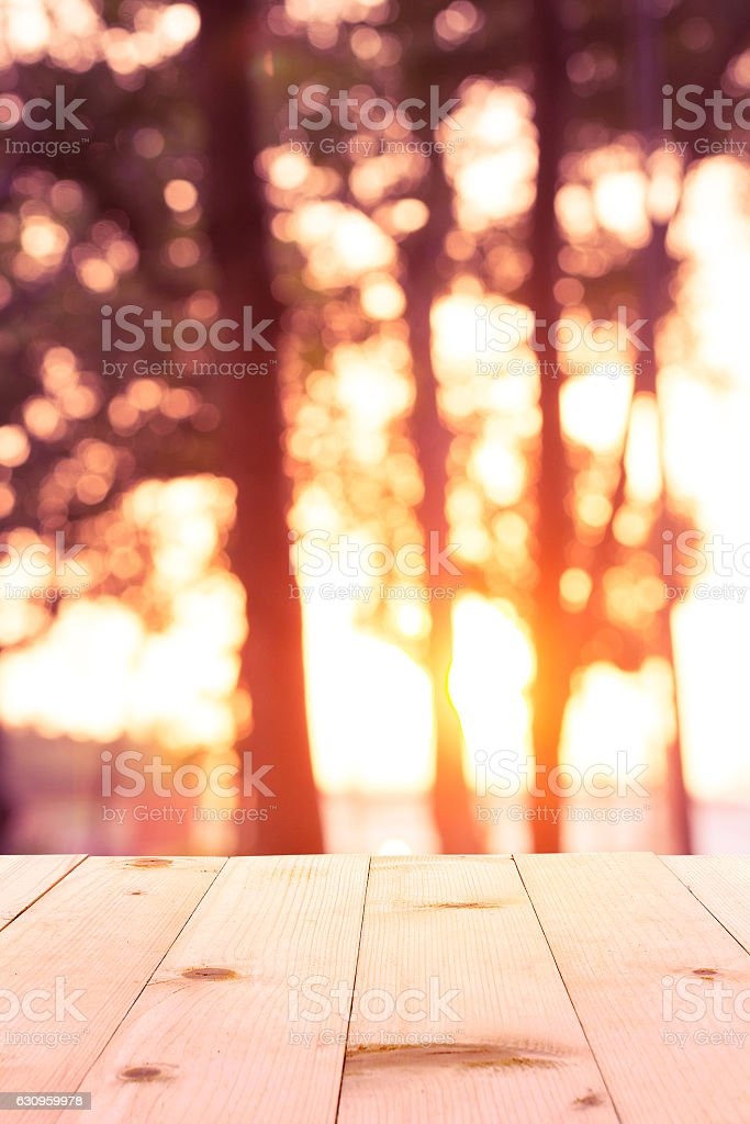 wooden table with tree and sunset blur background stock photo