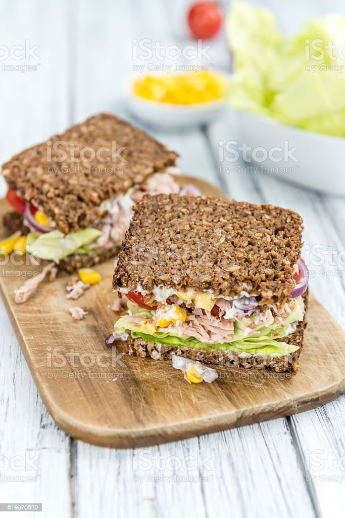Wooden table with Tuna sandwich (on wholemeal bread; selective f stock photo