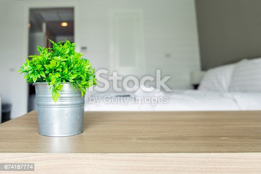 istock Wooden table with vintage vase plastic plant on bedroom 674187774