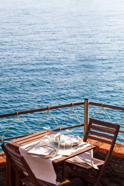 Holztisch mit weiß, Geschirr wasserund Stühle auf Ozean Restaurant – Foto