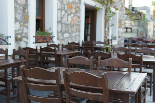 Wooden tables and chairs in a street cafe on a sunny day.