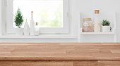 istock Wooden tabletop in front of blurred kitchen window, shelves background 1092539528