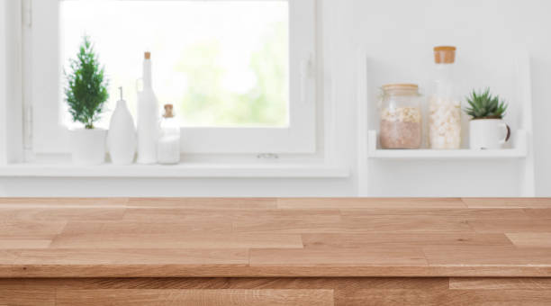 wooden tabletop in front of blurred kitchen window, shelves background - kitchen situations foto e immagini stock