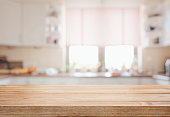 Empty wooden tabletop over defocused kitchen background with copy space