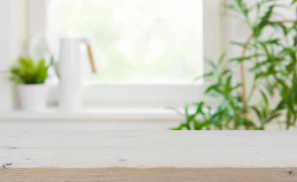 drewniany blat z kopiuj przestrzeni nad rozmytym tłem okna kuchennego - selektywna głębia ostrości zdjęcia i obrazy z banku zdjęć