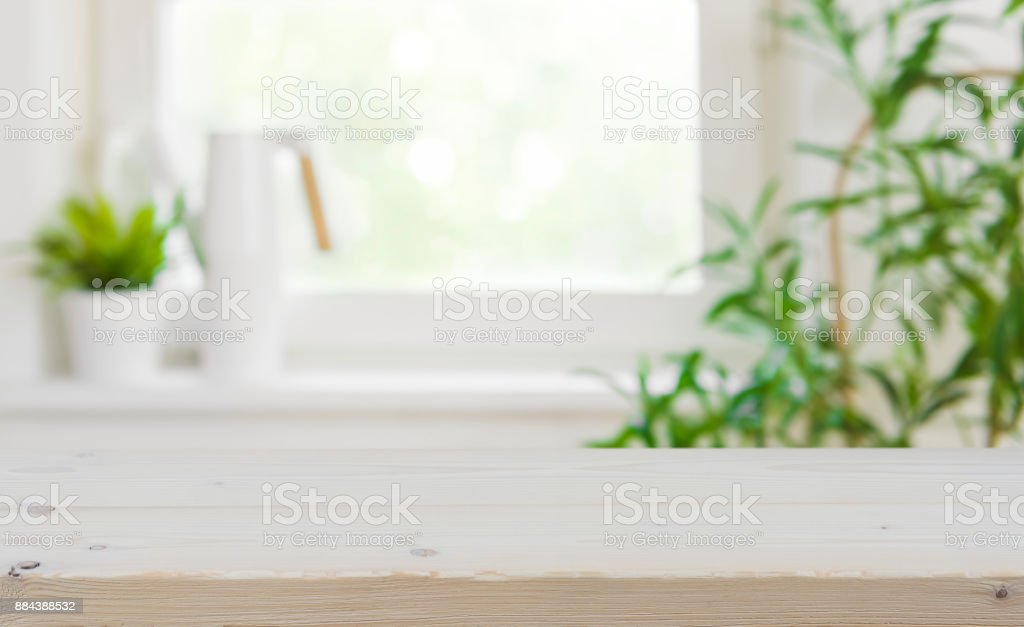 Wooden tabletop with copy space over blurred kitchen window background stock photo