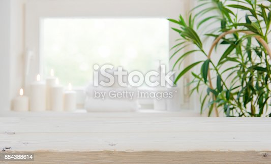 istock Wooden tabletop with copy space over blurred spa window background 884388614