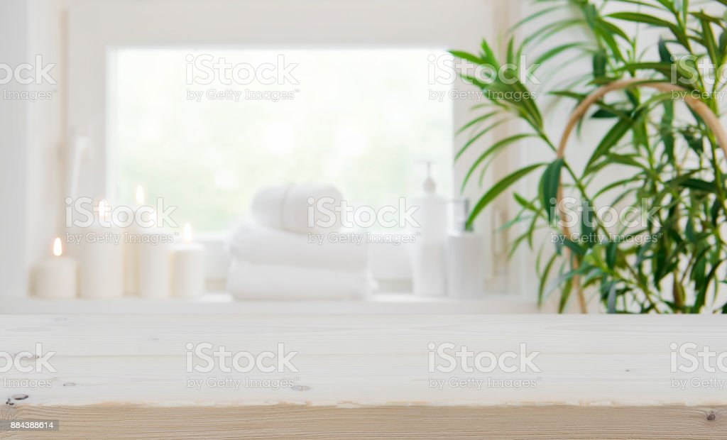Wooden tabletop with copy space over blurred spa window background stock photo