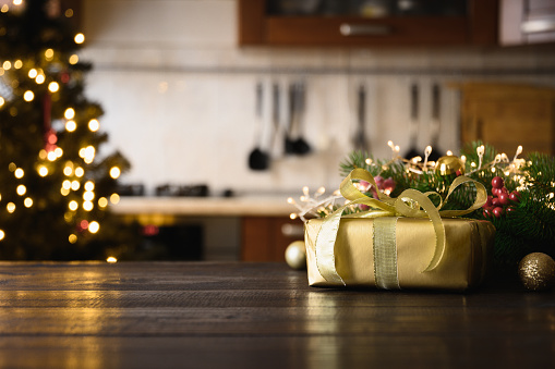 Wooden tabletop with gold gift Christmas decoration and blurred modern kitchen as background for display or montage your products.