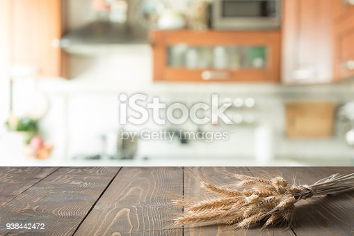 607472268 istock photo Wooden tabletop with wheat on blur kitchen room background for montage product. 938442472
