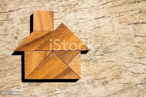 istock Wooden tangram puzzle in home shape for dream home or happy life concept 815111664