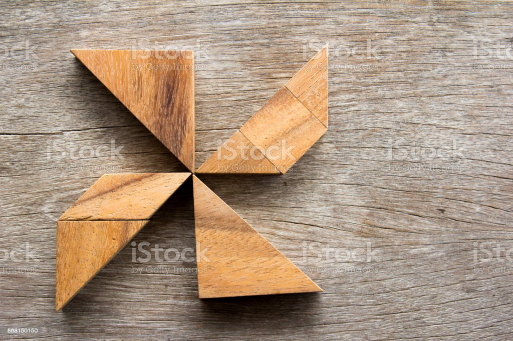 Wooden tangram puzzle in pin wheel shape background stock photo