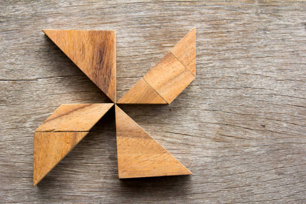 wooden tangram puzzle in pin wheel shape background - abstract logo stock photos and pictures