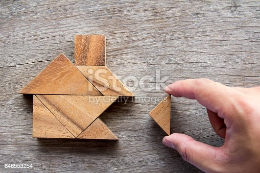 istock Wooden tangram puzzle wait to fulfill home shape for build dream home or happy life concept 646553254