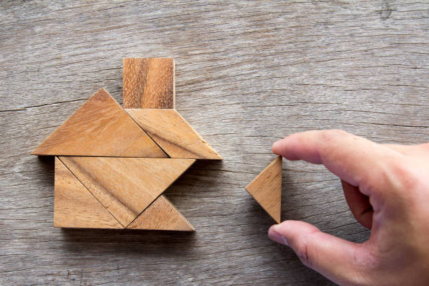 wooden tangram puzzle wait to fulfill home shape for build dream home or happy life concept - incomplete stock pictures, royalty-free photos & images