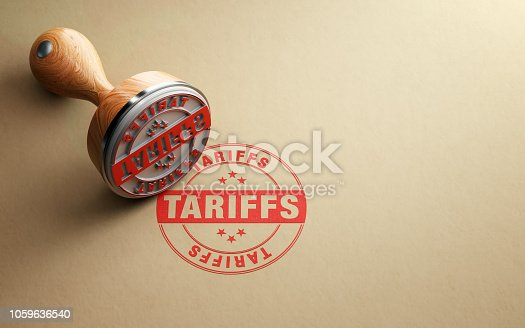 Wooden tariffs stamp is sitting on recycled paper background. Horizontal composition with selective focus and copy space.