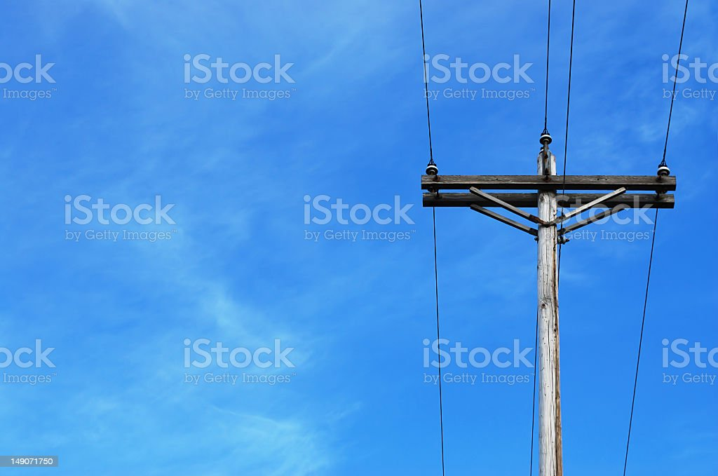 A wooden telephone pole with the view of the sky stock photo
