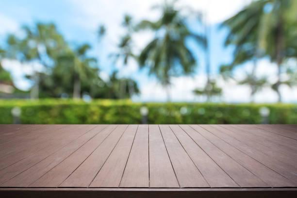 holzterrasse und tropischen garten abstrakten hintergrund - palmengarten stock-fotos und bilder