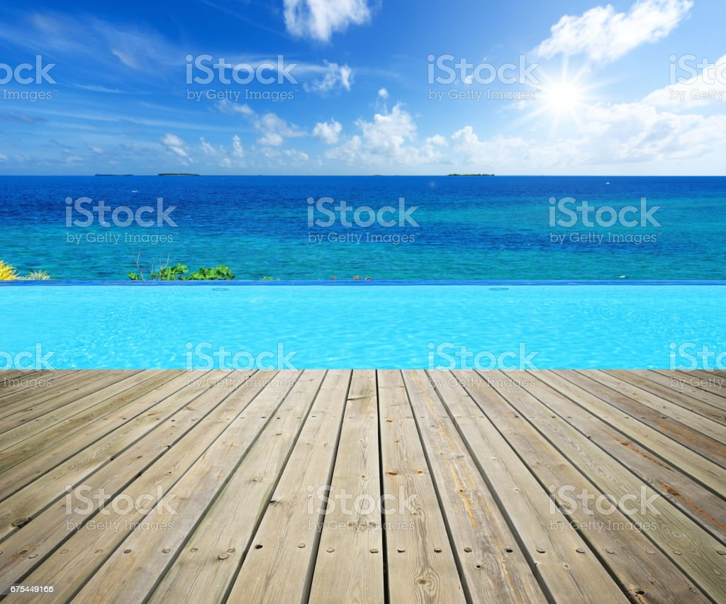 Wooden terrace beside infinity pool royalty-free stock photo