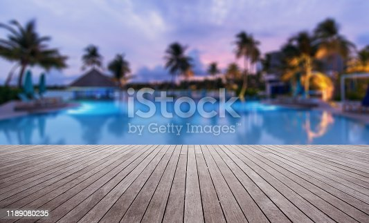 Wooden terrace beside tropical resort swimming pool at dusk