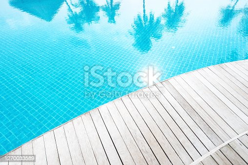 Wooden terrace beside tropical resort swimming pool