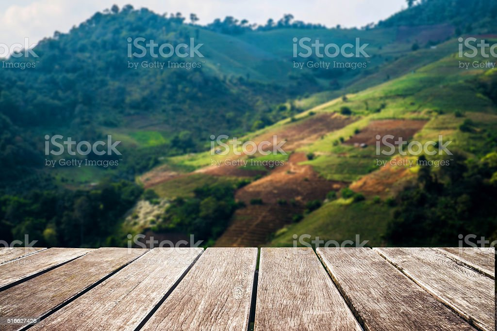 Wooden terrace with blurred defocus landscape of mountain, vintage tone stock photo