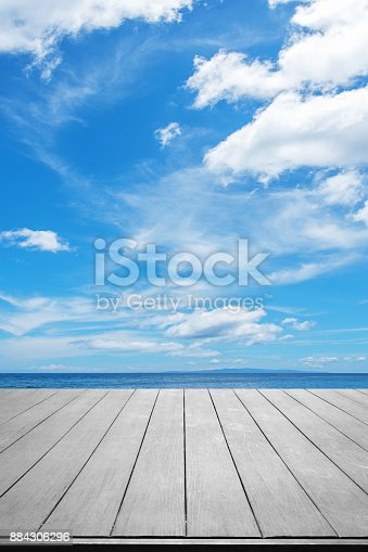 677933036 istock photo Wooden terrace with tropical ocean and blue sky background 884306296