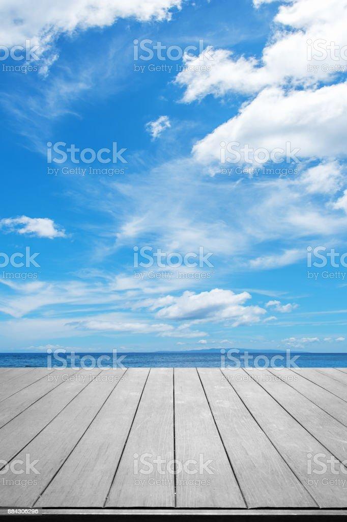 Terraço de madeira com oceano tropical e o fundo do céu azul - foto de acervo